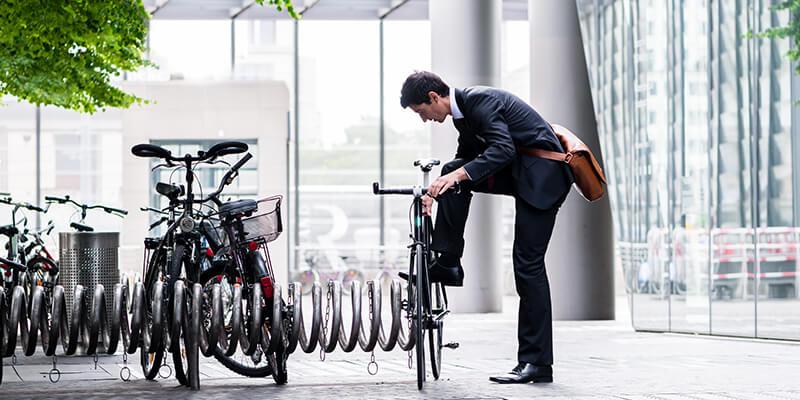 Businessman putting bike in rack