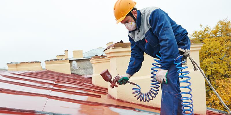 Man Spraying Red Roof